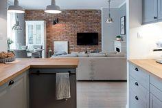 Z kuchni zaaranżowanej w otwartej przestrzeni dziennej rozciąga się widok na salon i jego główną dekorację - ścianę z...