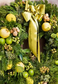 An overscale wreath dotted with apples, lemons, and nuts, as well as Hypericum berries and osage oranges.