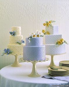 Ambiance~  Freesia Wedding Cakes  A fresh alternative to a single grand confection -- are adorned with sprigs of sugar freesia in yellow, lavender, and white. The cakes are iced in the same colors, but paired with a differently hued flower. A Swiss-dot motif piped onto the fondant~  (Photo Credit: Sang Ann; marthastewart.com)  (410) 819-0046  www.maryannjudy.com