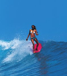 Surfer girl in a bikini surfing a wave on a pink surfboard. //Manbo