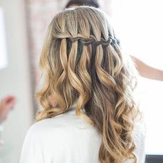 Looking for wedding hair ideas? This stunning half up half down hairstyle goes perfectly with a veil. The waterfall braid pairs perfectly with added curls.