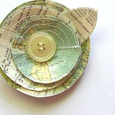 Maps turned flower.  This pin is made from vintage paper which has first been covered in clear vinyl. The Posie petals are cut and shaped by hand and machine stitched. The stitching gives the paper and vinyl a nice texture and also makes it very durable. A vintage button centers the layers of petals and leaf.