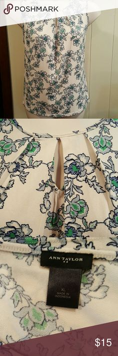 Ann Taylor Sleeveless Blouse Off white blouse has blueish gray and green flowers. Gathers at the neckline with a keyhole element to add interest. Ann Taylor Tops Blouses