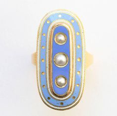 An 18 carat gold oval mourning ring with baby blue and white enamel (the white symbolizing the loss of a child and the blue is because Anne was considered to be royalty in the hearts of her family) decorated with three natural pearls in the center panel, made in memory of 'Anne Bayley, who died on the 29th of December, 1789 aged 16 years', England, 18th century.