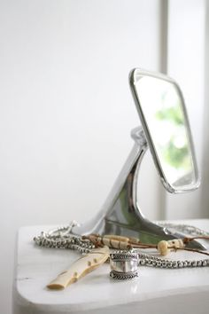 This is a vintage mirror from a car that has been repurposed into a makeup mirror. What a smart great idea for something that would otherwise not be used and abandoned in a junk lot!