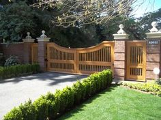This custom wood gate was installed with two matching pedestrian gates on both the sides. #wood #custom #gate