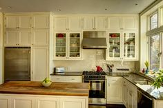 """Perimeter countertop is CaesarStone quartz in color Lagos Blue. Island countertop is Walnut. Backsplash is ANN SACKS Earthenware Elements,105 antique white crackle 3"""" x 6"""" subway tile. Cabinets: Shaker style doors painted in Benjamin Moore OC-85 Mayonnaise."""