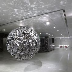 John Powers http://johnpowers.us/ creates geometric installations & sculptures that use simple (styrofoam, metallic...) blocks to form interesting patterns with depth & form (can also be with varying shades of colors & lights inside)