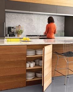 """Kitchen Island The streamlined kitchen of this home -- just outside the Chicago area -- offers plenty of hidden storage; the island, built of red cedar and marble, houses the owner's collection of classic Heath Ceramics """"Coupe"""" tableware."""