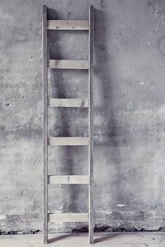grey wooden old ladder up against a grey concrete patina wall. simple textural beautiful.<3