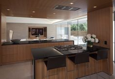 This warm and sophisticated kitchen remodel spotlights native Texas pecan custom cabinetry by Arete European Kitchens.