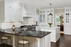 Bright white cabinetry lends an open, airy feel to this beautiful transitional kitchen. Glossy black countertops line the perimeter of the kitchen, adding eye-cathcing contrast to the space.