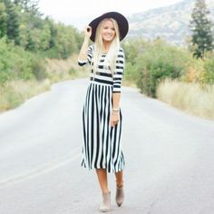 A woman on the road dressed in a black and white stripped dress