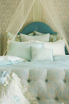Turquoise headboard. Pale bed linens.