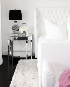 Pure by Ami Mckay: Chic black and white bedroom with glamorous accents. A white tufted wingback bed is ...