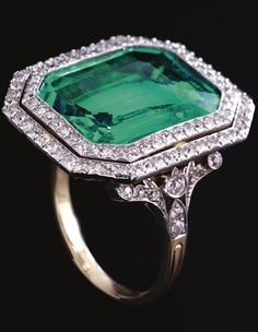 A very Fine emerald and diamond ring, circa 1910. The step-cut emerald weighing approximately 9.50 carats set within a double frame of circular-cut diamonds, highlighted by similarly-set shoulders, to a pierced scroll gallery. ~ETS