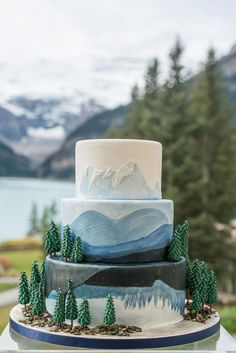 nature inspired wedding cake with trees and blue hand painted mountains at lake . - nature inspired wedding cake with trees and blue hand painted mountains at lake louise Sie sind an d - Pretty Cakes, Cute Cakes, Beautiful Cakes, Amazing Cakes, Mountain Cake, Mountain View, Nature Cake, Nature Inspired Wedding, Nature Wedding Cakes
