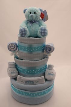 3 Tiered Boy Nappy Cake, packed with practical items for any new parents to be! included is a fleece blanket, muslin cloths, weaning spoons, soft toy and more. Take a look at our boy collection!