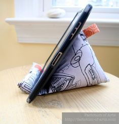 """As promised here is the Tutorial to make a iPhone/iPad (or other electronic device) stand I posted last week. Materials: Fabric 12"""" x 9"""" Cotton 2-3 cups of rice Pellon Ultra Firm 1 1/4"""" x 5 3/4"""" Po..."""
