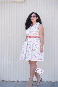 Tanesha Awasthi (formerly Girl with Curves plus size blogger) wearing a Flamingo print dress, pink sunglasses, ankle strap heels and flamingo print bag.