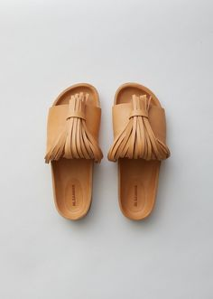 Honey-brown slide sandals in smooth, grain-free leather, designed with vamp-strap fringes pulled through tab slots for a tasseled effect. Jil Sander Fringe Sandals in tan leather from La Garconne.   #sandals #ontrend #tanleather #forsummer #lagarconne