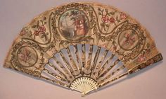 This 18th century fan has ivory or bone sticks, gilt and silvered inlaid work with putti (cupids) and aristocratic ladies in architectural settings.
