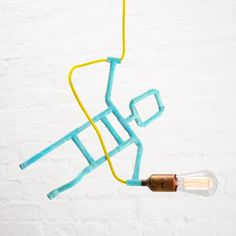 Designer pendant lamp in white brick loft apartment. Joyful and funny design in amazing turquoise patina with yellow braided cord and vintage Edison bulb. Available in Zapalgo online store.