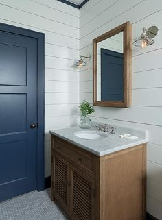 An eye catching navy blue 3 panel door opens to a white cottage bathroom fitted with a Restoration Hardware Shutter Single Vanity placed on carrera marble hex floor tiles and topped with a carrera marble countertop finished with a round sink and polished nickel cross handle faucet fixed beneath a brown oak beveled mirror lit by 20th C.