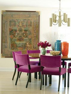 amazing pink upholstered chairs paired with gold light fixture and dark wood table