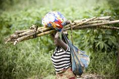 A woman carries her belongings and some sugar cane as she flees recent fighting in North Kivu province's Rutshuru region in Democratic Republic of the Congo.  ©UNHCR/S.Modola