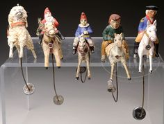 FIVE GERMAN PAPIER MACHE HORSES WITH RIDERS BALANCE TOYS.