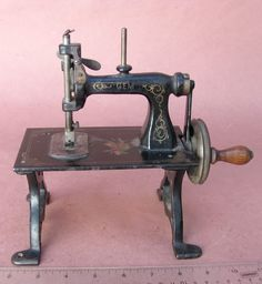 """American Gem Sewing Machine / Toy Sewing Machine / TSM   This is a great looking and very hard to find antique toy sewing machine / TSM.  The overall condition of this example is very nice.  These machines can also be found marked """"Gem"""", as this one is, or """"American Gem"""".  The cast iron base was designed to resemble a real treadle sewing machine stand."""