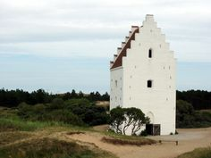 Skagen in Denmark holds a special place in my heart. The Tilsandede Kirke is a church located south of Skagen. The tall white building that is visible at the top of a sand hill is only it's bell tower. The rest of the church was buried by migrating sand dunes around the 1400s!