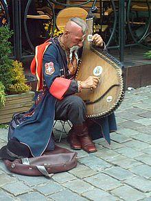 A Ukrainian Cossack (Ostap Kindrachuk) playing the bandura and wearing traditional clothing.