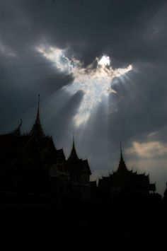 Angel shape appears in break in the clouds above the Grand Palace in Bangkok, Thailand