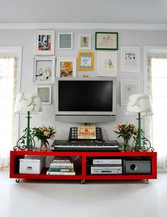 Hiding TVs In Plain View – Incorporate the TV into a salon style picture arrangement. The first time I saw this successfully employed, and it was so effective visually that now I employ it in nearly every home I help to decorate. Surrounded by pieces of art with similar shape or size frames, the TV blends into the background rather than dominating the wall. The red shelf shown above is actually from Ikea, in the LACK range. We took out 2 shelves, laid it on it's side and added casters.