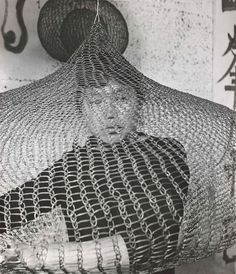 RUTH ASAWA, Asawa working inside on one of her crocheted wire sculptures, 1957. Photography by Imogen Cunningham. / FAMSF