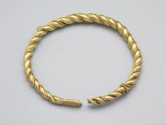 Viking gold arm-ring of plaited wires (2 thick & 2 thin, unwound in places); gold; 1 of terminals left, flat with row of punched paired triangles. Deposited circa 970 at the Isle of Man, Scotland.