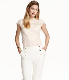 Short-sleeved top in jersey with a sheen. Lace yoke, lace sleeves, and opening at back of neck with button.