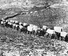 Wagon Train pushing across the western prairies of the United States on their…
