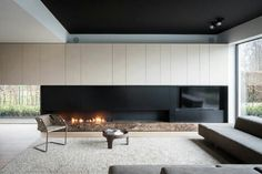 Like: modern, clean fireplace (fire is on small stones and not logs - which makes it cleaner); overall view not overly dark -Do not like: the chair seems too minimalist Linear Fireplace, Modern Fireplace, Fireplace Design, Gas Fireplace, Fireplaces, Fireplace Ideas, Fireplace Outdoor, Black Fireplace, Fireplace Inserts
