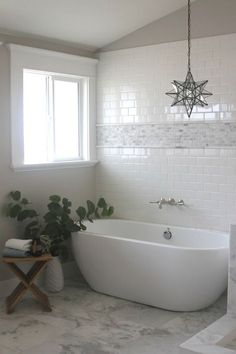 Gorgeous bathroom with subway tiled wall bordered with a mini marble mosaic tile accent tiles alongside wall mount tub filler across from a freestanding egg shaped tub.
