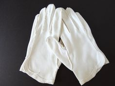 These vintage, soft white dress gloves are a heavy, barely stretchy fabric that has been hand stitched. They have a scalloped applique detail at the hem