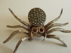 Antique art deco spider brooch from 1920s; sterling silver, marcasite, and ruby.