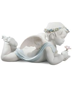 "This figurine from Lladro features a naturalistic representation punctuated by the delicate color palette on the angel's flower garland. | Porcelain | Wipe with cloth | Imported | Dimensions: 10.25"" x"