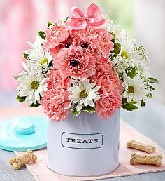 Put the crowning touch on her day with our pretty, pampered pooch, newly designed in a keepsake treats tin! Crafted with fresh pink carnations, white daisy poms and more, your favorite puppy lover can later re-use the canister for dog treats or as a charming cookie jar.