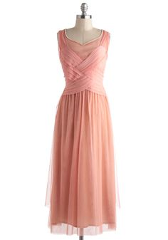 Sleeveless peach tulle dress lined in nude with pearl-edged diamond neckline, trellis-woven pink pleated crepe front bodice with dropped waist and pleated sash ties, 4 pearl button closure at back, and tea length gathered skirt with shorter panel at each side. Make all in pink, and continue woven bodice to back!! 100% nylon (tulle & crepe)/100% cotton (lining), from ModCloth