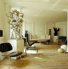/\ /\ . Frédéric Méchiche . Paris Apartment . Living Room . Bare wooden floorboards and white panelled walls create a neutral canvas for Méchiche's collection of period and modern furniture and sculpture by Jean Dubuffet, Joseph Beuys, Pierre Soulages and Cesar and Jean Arp.
