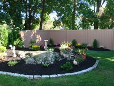 Complete Design with Cobblestone Borders with plantings and Custom Vinyl Fence with wood grain look | Yelp