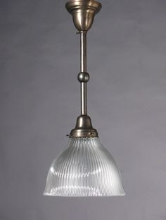 "Circa 1915, this Holophane Pendant is of prismatic glass and Signed "" Holophane"". 23"" drop x 9 3/4"" diameter x 8"" shade depth. $560.00    Holophane is one of the oldest of lighting-related products in the world; founded in 1898 in London, England. They are a UK (based in Milton Keynes, England) and US manufacturer (based in Newark, Ohio) of lighting fixtures for commercial, industrial, outdoor, and emergency applications. The hallmark of their products is a glass reflector/refractor."